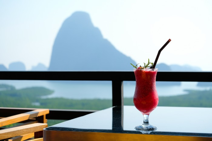 photo of a cocktail on a table with the silhouette of a mountain in Da Nang on the background