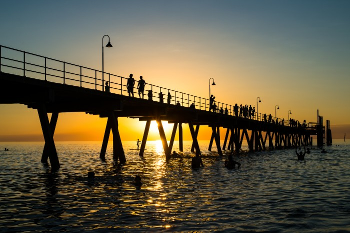 Adelaide: sunset over the ocean in Glenelg with the boardwalk in sight