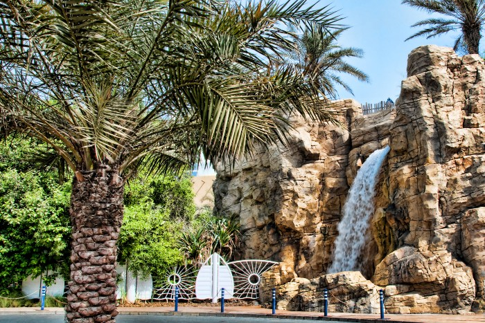 entrance gate to the Wadi Wadi Water Park with palms and a waterfall