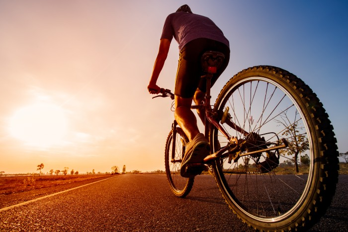 a photo of a man on a bike in the sunset