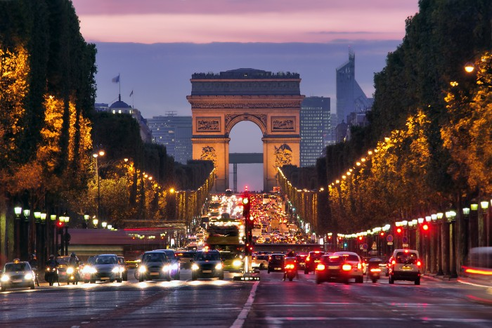 wide street in Paris with cars, lights, and the Arc du Triomphe at the back