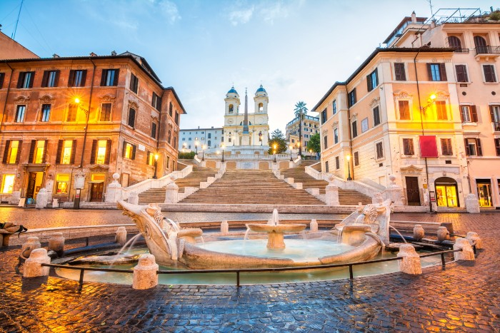 A semi-bird's eye view of the Spanish Steps with buildings and a fountain in the frame