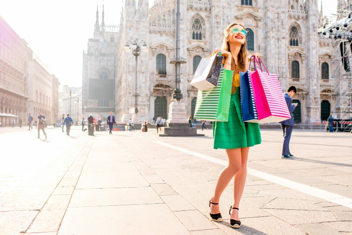 a woman carrying shopping bags in the street of Milan