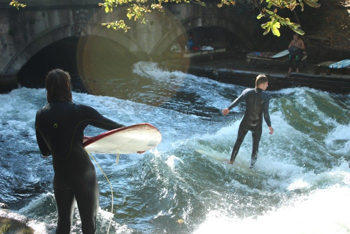 two people surfing on the river