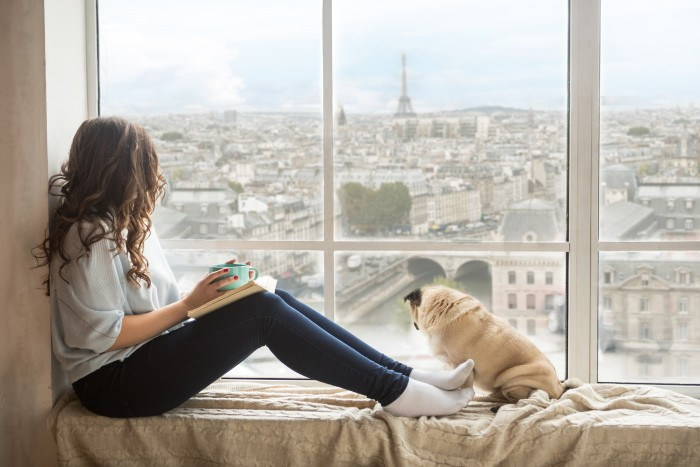 Paris: girl sitting with her dog by the window