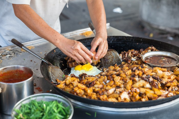 Penang: a local is breaking an egg into a dish he is cooking