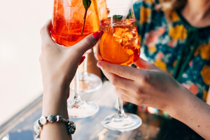 do's and don'ts when travelling in Venice: 2 glass of aperol spritz raised
