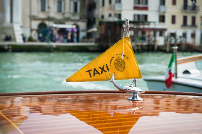 do's and don'ts when travelling in Venice: the flag of a water taxi